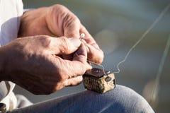 Le pêcheur met l'amorce sur un crochet de canne à pêche Images libres de droits
