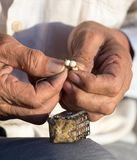Le pêcheur met l'amorce sur un crochet de canne à pêche Image stock