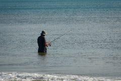 Le pêcheur pêche des poissons en mer sur un poteau de pêche se tenant dans l'eau images libres de droits