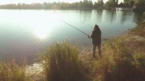 Le pêcheur pêche sur la berge au soleil Pêche barbue d'homme du rivage par temps beau banque de vidéos