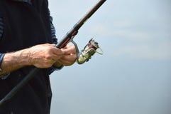 Le pêcheur prépare la canne à pêche Photo stock