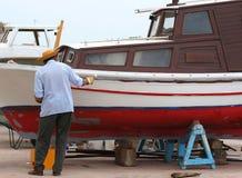 Le pêcheur répare le bateau photographie stock libre de droits