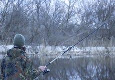 Le pêcheur regarde l'eau qu'il dispose à jeter l'amorce Image libre de droits