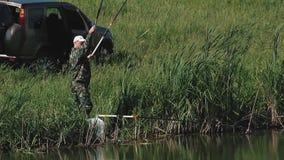 Le pêcheur retire la canne à pêche avec les poissons banque de vidéos