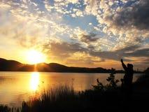 Le pêcheur se tenant sur un rivage avec le soleil de fond rayonne Image libre de droits