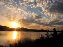 Le pêcheur se tenant sur un rivage avec le soleil de fond rayonne Photo stock