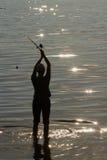 Le pêcheur sur le lac jette une tige de rotation Photographie stock libre de droits