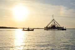 Le pêcheur vont à la silhouette de flottement de maison Image stock