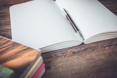 Le pagine in bianco bianche schizzano il libro sulla tavola di legno Immagine Stock