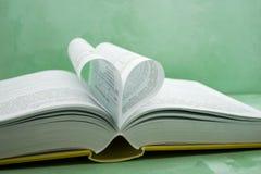 Le pagine di un libro hanno curvato in una figura del cuore fotografia stock