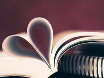Le pagine molli del fuoco del primo piano di un libro hanno curvato in una forma del cuore fotografia stock libera da diritti