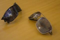 Le paia degli occhiali da sole si trovano su una tavola di legno fotografia stock