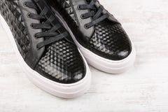 Le paia del ` nero delle signore mettono in mostra le scarpe di cuoio su fondo di legno bianco Fotografia Stock Libera da Diritti