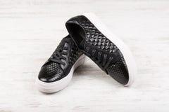 Le paia del ` nero delle signore mettono in mostra le scarpe di cuoio su fondo di legno bianco Fotografie Stock