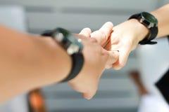 Le paia delle mani che si tengono e l'orologio delle coppie Fotografie Stock
