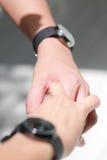 Le paia delle mani che si tengono e l'orologio delle coppie Fotografie Stock Libere da Diritti
