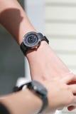 Le paia delle mani che si tengono e l'orologio delle coppie Immagini Stock