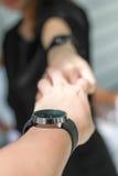 Le paia delle mani che si tengono e l'orologio delle coppie Fotografia Stock