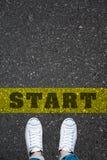 Le paia delle scarpe che stanno su una strada con la parola COMINCIANO Immagine Stock Libera da Diritti