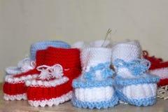 Le paia di bianco fatto a mano e di rosso hanno tricottato le pantofole fotografie stock libere da diritti