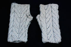 Le paia di lana fatta a mano hanno tricottato i guanti su fondo nero Fotografia Stock