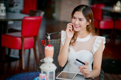 Le paiement en ligne, la fille 's remet tenir une carte de crédit et un usin Image libre de droits