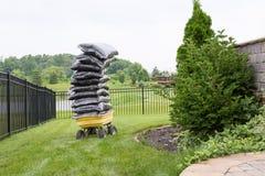 Le paillis dans les sacs a empilé la haute sur un chariot dans le jardin Photos libres de droits