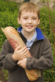 Le Pain. Young French boy holding a loaf of bread - le pain Royalty Free Stock Images