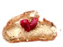 Le pain avec du beurre et le coeur rouge forment le symbole d'amour de marmelade Images stock