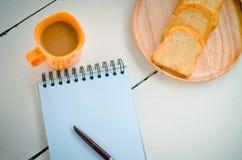 Le pain, café, le carnet, crayon sur le concept de bureau font une pause - la vie toujours images libres de droits