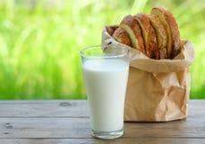 Le pain a coupé des morceaux avec le verre de lait sur la table en bois Photos libres de droits