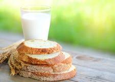 Le pain a coupé des morceaux avec le verre de lait sur la table en bois Photo stock
