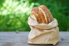 Le pain a coupé des morceaux dans le sac de papier sur la table en bois Photographie stock