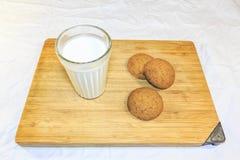 Le pain a coupé en morceaux sur un conseil en bois à côté d'un verre de lait photo stock