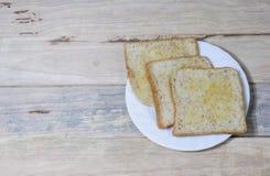 Le pain dans le plat blanc a mis dessus le bureau en bois Photographie stock libre de droits