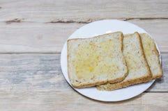 Le pain dans le plat blanc a mis dessus le bureau en bois Photos libres de droits