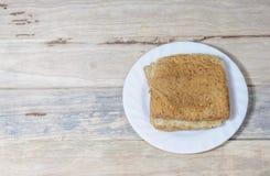 Le pain dans le plat blanc a mis dessus le bureau en bois Image libre de droits