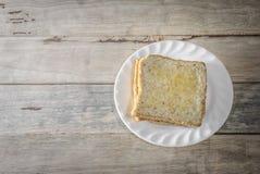 Le pain dans le plat blanc a mis dessus le bureau en bois Images libres de droits