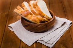 Le pain de coupe coûte sur une serviette de toile dans une cuvette en bois photos libres de droits