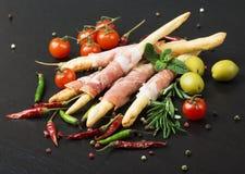 Le pain de Grissini baton avec le prosciutto sur un fond noir avec le romarin, le poivre et les olives images libres de droits