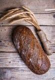 Le pain et le blé rustiques sur un vieux vintage planked la table en bois Fond déprimé foncé avec l'espace de texte libre Image stock