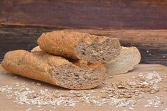 Le pain et les grains sur le fond en bois photos stock