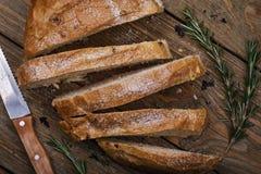 Le pain fraîchement cuit a coupé en tranches avec le plan rapproché de romarin Photo libre de droits
