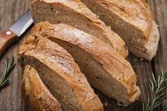 Le pain fraîchement cuit a coupé en tranches avec le romarin Images libres de droits