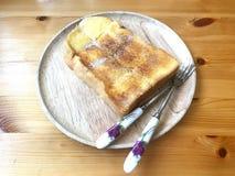Le pain grillé coupé en tranches a complété avec du beurre et le sucre dans le plat en bois photo libre de droits