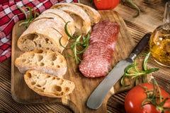 Le pain italien de ciabatta a coupé dans les tranches avec le salami Photographie stock
