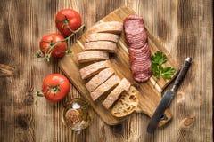 Le pain italien de ciabatta a coupé dans les tranches avec le salami Photos stock