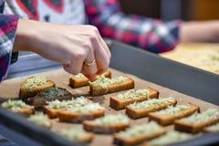 Le pain noir avec du fromage et des assaisonnements, la fille arrose le pain coupé en tranches image libre de droits