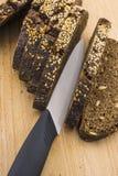 Le pain noir a découpé le ‹en tranches d'†de ‹d'†sur une planche à découper Photographie stock