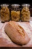 Le pain s'est étendu sur un hachoir, avec des bols de pâtes dans le backgrou Photos stock
